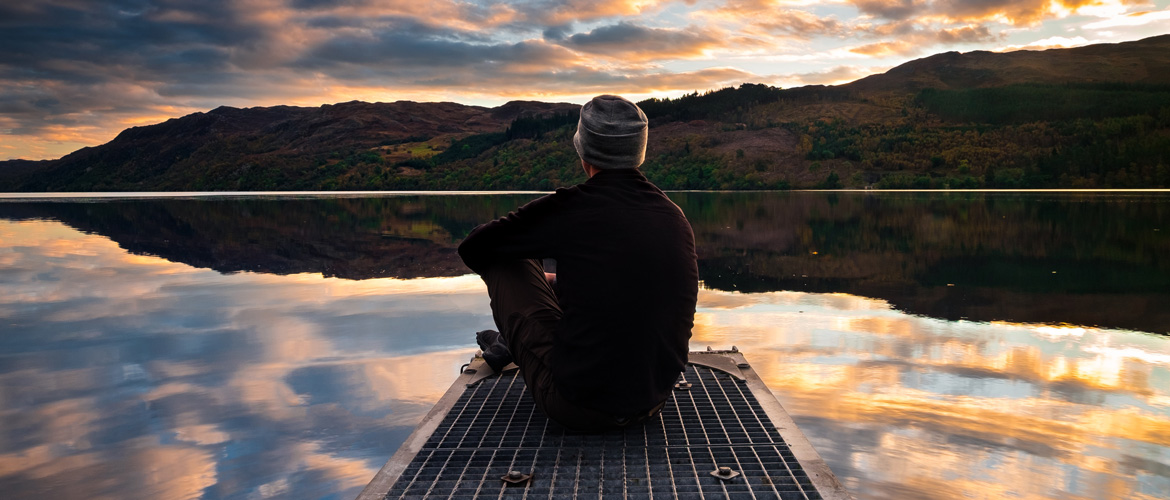 Highly Sensitive Person sitting by a calm lake.